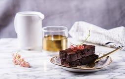Торт пирожного шоколада с ягодами красной смородиной и чашкой кофе Стоковая Фотография