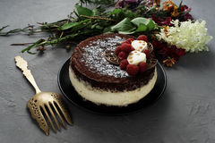 Торт покрытый с шоколадом украсил поленики, с букетом цветков на серой предпосылке Стоковые Изображения RF