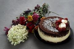 Торт покрытый с шоколадом украсил поленики, с букетом цветков на серой предпосылке Стоковые Фотографии RF