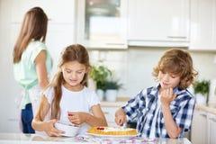 Торт плодоовощ выпечки мальчика и девушки Стоковые Изображения