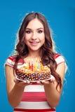 Торт удерживания женщины с свечами Стоковая Фотография