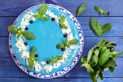 Торт украшенный с голубыми сливк, мятой и голубиками Стоковые Изображения