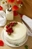 Торт украшенный с клубниками на предпосылке вазы с цветками вертикально Стоковая Фотография RF