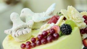 Торт украшенный с figurines птиц, цветков, ягод и сливк акции видеоматериалы