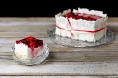 Торт ягоды и его часть на стеклянных пластинках кладя на деревянный стол На черной предпосылке Стоковое Изображение RF