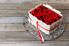 Торт ягоды с красным студнем завязал ленту красного цвета и белизны на стеклянном блюде Деревянная предпосылка Стоковая Фотография RF