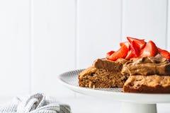 Торт Vegan с темными шоколадом, клубниками и сливк шоколада на белом блюде стоковое изображение