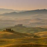 Тосканская обрабатываемая земля с виллами и деревнями на зоре Стоковые Изображения RF