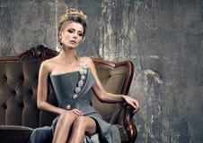 Тоскливость времени партии Сиротливая красивая молодая женщина в сером усаживании платья вечера стоковое фото
