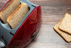 Тостер с провозглашанным тост концом хлеба вверх по взгляд сверху на деревянной предпосылке, оборудовании кухни Стоковое Изображение RF
