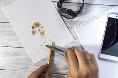 Точит карандаш с ножом Стол часов, блокнота и мобильного телефона стоковые изображения rf