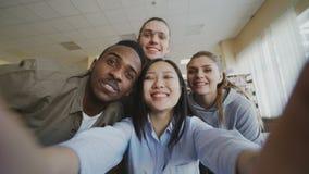 Точка зрения азиатской девушки держа smartphone принимая фото selfie с жизнерадостными одноклассниками и имеет потеху в университ акции видеоматериалы