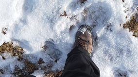 Точка зрения Hiker Крупный план замедленного движения идя на путь горы между травой и снегом