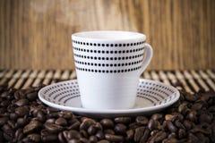 Точки польки чашки стоя на кофейных зернах нерезкости Стоковые Изображения RF