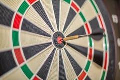 Точная видимость дротика ударяя центр цели, dartboard и дротика, запачканной предпосылки стоковое изображение