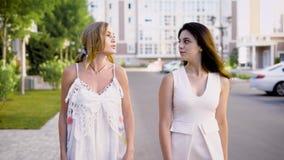 2 точных смотря женщины нося белые платья идут вниз с переулка, говорящ о жизни и событиях сток-видео