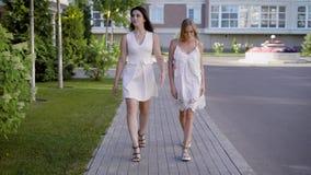 2 точных смотря женщины нося белые платья идут вниз с переулка, говорящ о жизни и событиях видеоматериал