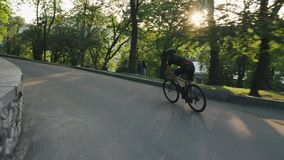 Тощий атлетический велосипедист восходя холм в парке Велосипедист покатый в парке Замедленное движение велосипедиста дороги акции видеоматериалы