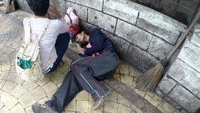 Тощий бездомный человек присутствуемый на пешеходом дамы который упал fainted на тротуаре акции видеоматериалы