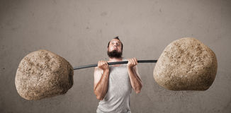 Тощий парень поднимая большие весы камня утеса Стоковые Изображения