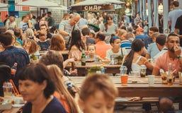 Толпа голодных людей есть еды вокруг таблиц внешних Стоковое фото RF