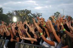 Толпа концерта веселя за барьером стоковое фото