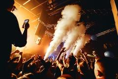 Толпа силуэта ночного клуба вручает вверх на этапе пара стоковое изображение