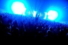 Толпа силуэта ночного клуба вручает вверх на этапе пара confetti стоковое фото rf
