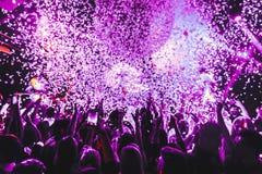 Толпа силуэта ночного клуба вручает вверх на этапе пара confetti стоковые изображения