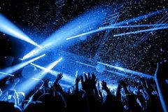 Толпа силуэта ночного клуба вручает вверх на этапе confetti стоковые изображения