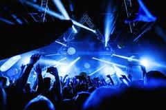 Толпа силуэта ночного клуба вручает вверх с entertanment мухы стоковая фотография
