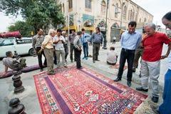 Толпа людей говоря о старом ковре Стоковое фото RF