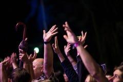 Толпа людей с их руками вверх во время рок-концерта на темной предпосылке стоковое изображение rf