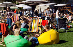 Толпить партия с расслабляющими людьми под зонтиками на зеленой гостиной Стоковое фото RF