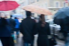 Толпы улицы людей пересекая на дождливый день в городе Стоковые Фото