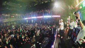 Толпы людей веселя на партии в ночном клубе оператор Хозяин на этапе сток-видео