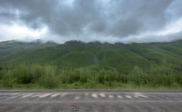 Толстые верхние части горы крышки дождевых облако вдоль дороги гравия Стоковое Изображение RF