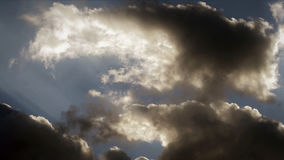 Толстые задумчивые облака с светлый загораться до конца стоковое изображение