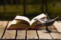 Толстый лежать книги открытый на деревянной поверхности, лампе сидя рядом с ей, красивой установке Aladin света ночи, волшебной к Стоковое фото RF