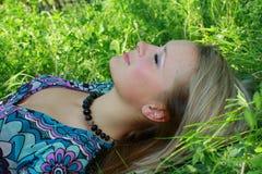 трава девушки кладет детенышей Стоковое Фото