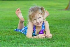 трава девушки кладя помадку Стоковое фото RF