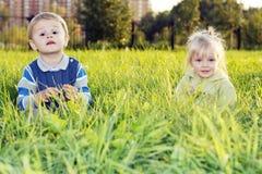 трава девушки мальчика Стоковые Фотографии RF