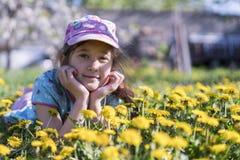 трава девушки цветка немногая лежа напольно Усмехаясь девушка лежа на поле с одуванчиками Стоковое Фото