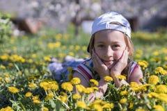 трава девушки цветка немногая лежа напольно Усмехаясь девушка лежа на поле с одуванчиками Стоковое фото RF