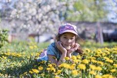 трава девушки цветка немногая лежа напольно Усмехаясь девушка лежа на поле с одуванчиками Стоковые Изображения
