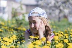 трава девушки цветка немногая лежа напольно Усмехаясь девушка лежа на поле с одуванчиками Стоковые Фотографии RF
