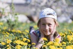 трава девушки цветка немногая лежа напольно Усмехаясь девушка лежа на поле с одуванчиками Стоковое Изображение RF