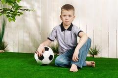 трава мальчика шарика Стоковое Изображение