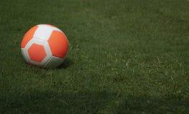 Трава оранжевого футбола футбола зеленая с экземпляр-космосом предпосылки игрока Стоковое Изображение