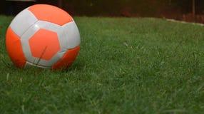 Трава оранжевого футбола футбола зеленая с экземпляр-космосом предпосылки игрока Стоковые Изображения RF
